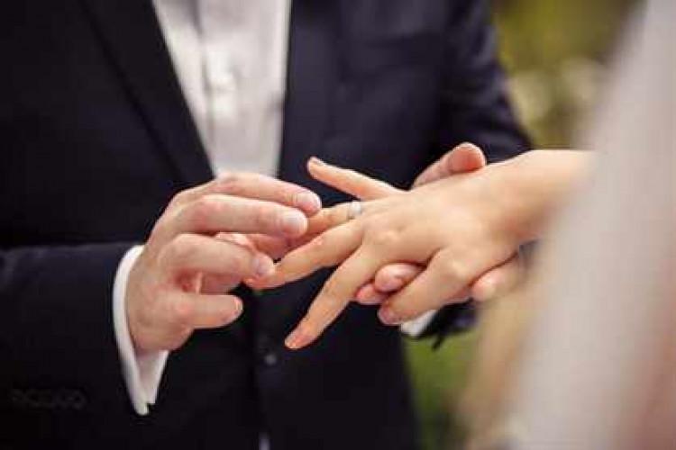 Жених надевает обручальное кольцо на руку невесты