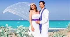 Couple in wedding day on beach sea with wind on veil